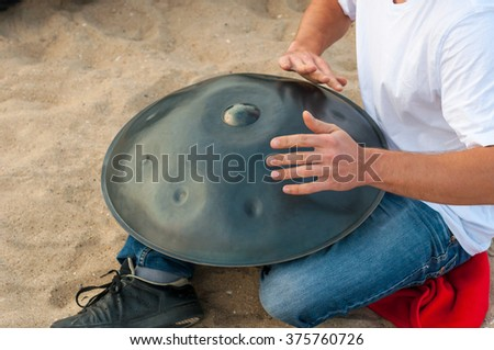 The drummer in action. guy sitting on the sand beach and playing handpan or hang. Hang is traditional ethnic drum musical instrument - stock photo