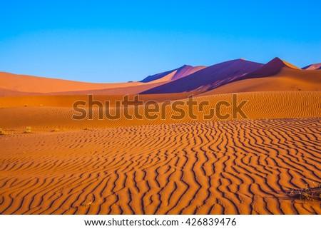 The dunes and sandy orange waves. Travel to Namibia. Namib-Naukluft National Park - stock photo
