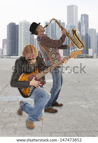 The duo of musicians with guitar and saxophone against the background of skyscraper - stock photo