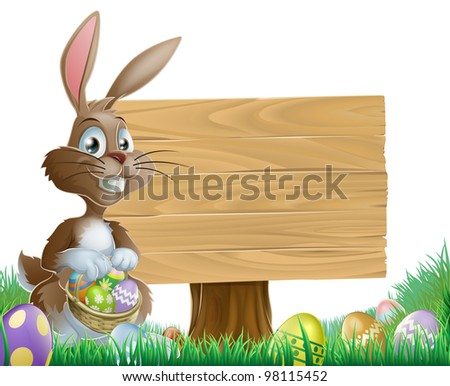 The Easter bunny holding a basket of Easter eggs with more Easter eggs around him by a wood sign board - stock photo
