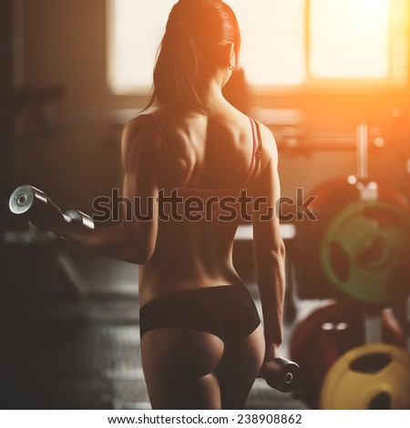 The effect of oil paints. Brutal athletic woman pumping up muscles with dumbbells. Brunette sexy fitness girl in pink sport wear with perfect body in the gym posing before training set - stock photo
