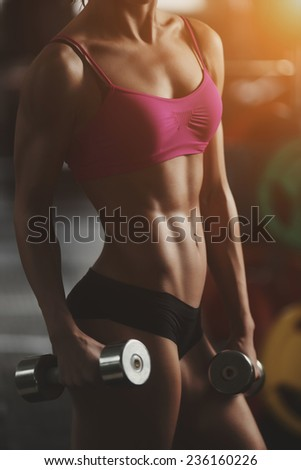 The effect of oil paints. Brutal athletic woman pumping up muscles with dumbbells. Part of body. Athletic young woman doing a fitness workout - stock photo