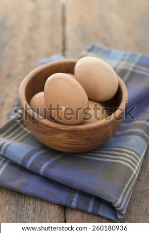 The eggs in wooden bowl. Placed on fabric