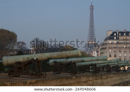 The Eiffel Tower in Paris, France. The tower stays in the background and there is a row of cannons in the foreground working as a leading line for the viewer. - stock photo