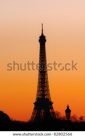 The Eiffel Tower silhouetted against a fiery sunset - stock photo