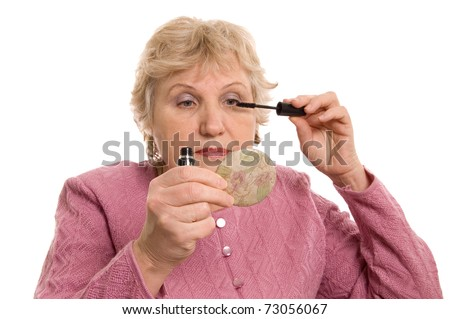 The elderly woman does a make-up - stock photo