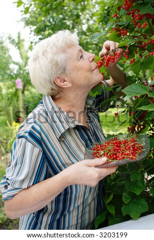 The elderly woman eats a currant