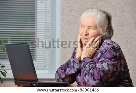 The elderly woman in front of the laptop. A photo in a room
