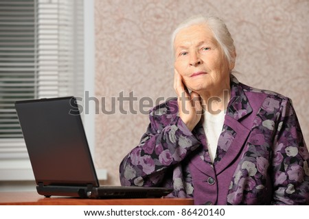 The elderly woman in front of the laptop. A photo in a room - stock photo