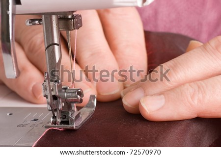 The elderly woman sews on the sewing machine - stock photo