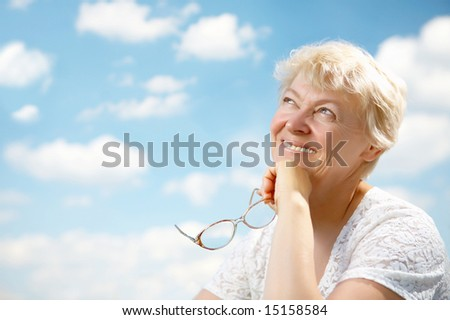 The elderly woman smiles and holds in hands glasses on a background of the blue sky - stock photo