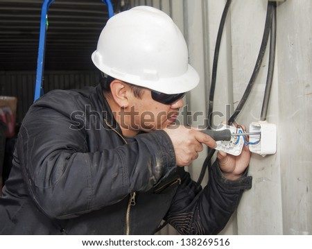 The electrician establishes an electrical wiring. Installation of equipment on production. - stock photo