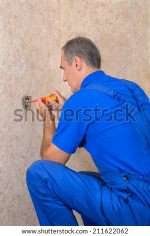 The electrician repairs electrical wall outlet - stock photo