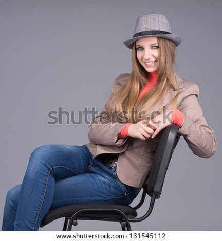 The elegant girl in a hat on a chair - stock photo