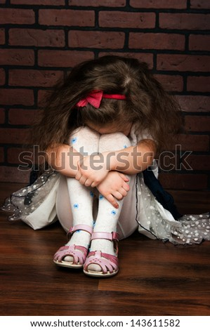 the elegant girl with wavy hair against a brick wall - stock photo