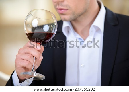 The elegant man in a business suit, drinking wine, sitting in a restaurant - stock photo