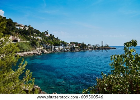The embankment of the Mediterranean Sea of France, near the Principality of Monaco, azure water, Cap-Dail, a sunny day, the quiet sea, the stony embankment, country houses, having a rest people