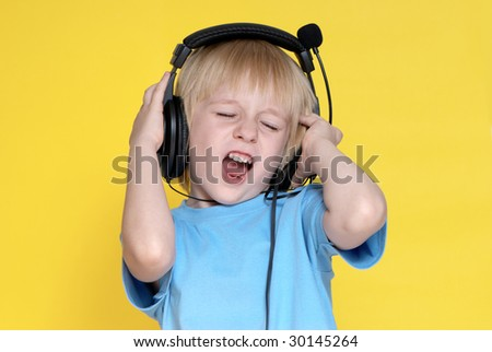 The emotional kid in ear-phones on a yellow background - stock photo