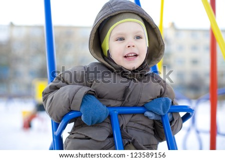 The emotional small child riding on a swing in winter - stock photo