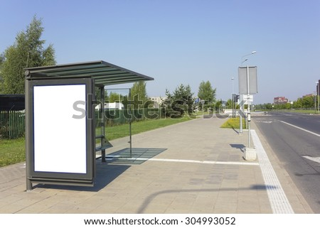 The  empty mass production bus-stop near  highway in the sleepy summer small city. Hot sunny day urban landscape.