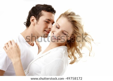 The enamoured young couple embraces on a white background - stock photo
