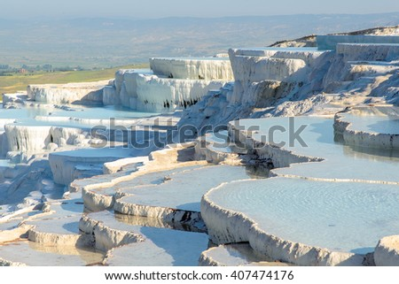The enchanting pools of Pamukkale in Turkey. Pamukkale contains hot springs and travertines, terraces of carbonate minerals left by the flowing water. The site is a UNESCO World Heritage Site. - stock photo