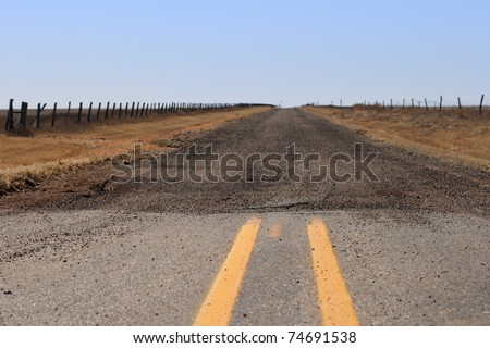 the end of the paved road where it turns into a gravel road extending to the Texas Panhandle horizon - stock photo