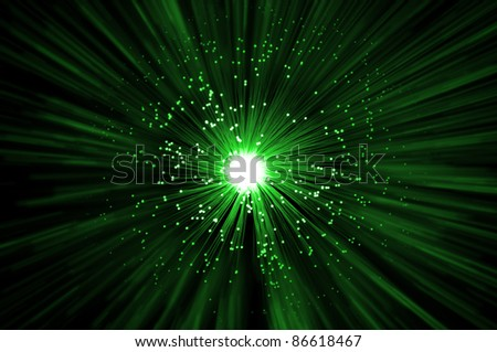 The ends of many illuminated green fibre optic strands emitting a green light blur effect from the centre against a dark background. - stock photo
