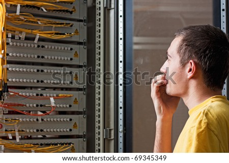 The engineer stand near optic cross box and with astonishment looks at a patch cords. - stock photo