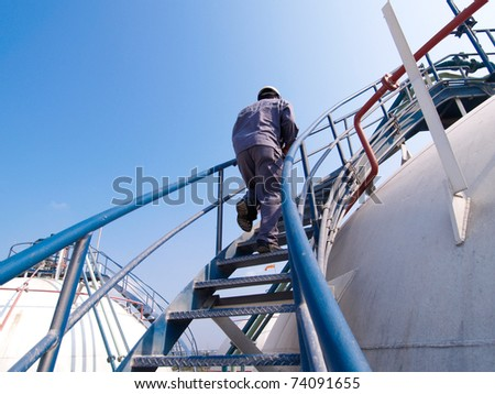 The engineer walking along the ladder of the refinery tank for checking valves and safety systems - stock photo