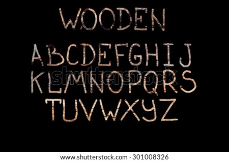 The English alphabet on a black background with wooden texture