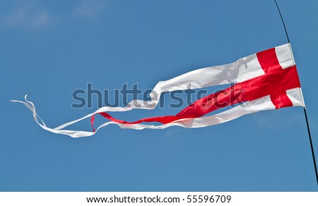 The English flag, the red cross of St George, flying as a pennant against  blue sky
