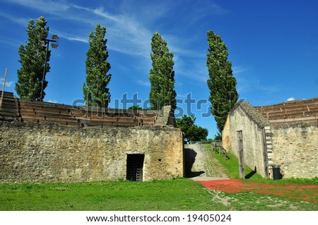 The Entrance ramp down into the remains of a roman amphitheatre in Martigny, southern switzerland. Poplars are planted around the periphery of the building