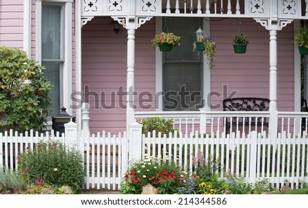 The entrance to an old Victorian home behind a white wooden gate flanked by daisies, red coneflowers, violas, astilbes, and yellow pansies. - stock photo