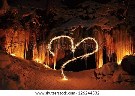 The entrance to the ice cave and Valentine heart - stock photo