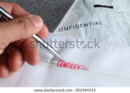 The envelope with red ink stamped with the word confidential in the scene the man hand in action of writing also represent the letter and symbol concept related idea. - stock photo