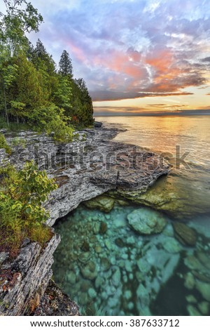 The ephemeral majesty of early morning is captured on the rocky Lake Michigan coastline of Door County, Wisconsin's Cave Point. - stock photo