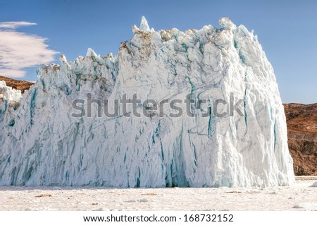 The Eqi Glacier in Greenland. - The Eqi is one of the most active glaciers in Greenland and it is constantly calving and breaking ice pieces into the fjord.  - stock photo