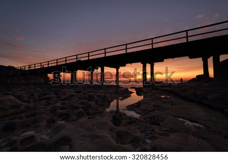The eroded cratered rocks under the bridge at Bare Island,  La Perouse Botany Bay as the sun sets - stock photo