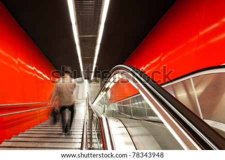 The escalator in motion. Motion blurred travellers. - stock photo
