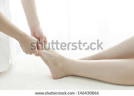 The esthetician who massages a foot