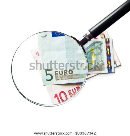 the euro currency under a magnifying glass  on white background - stock photo