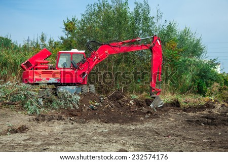 The excavator digs the earth, a cane and the tumbled-down trees, the equipment carries out planning of the district for further carrying out construction works. - stock photo