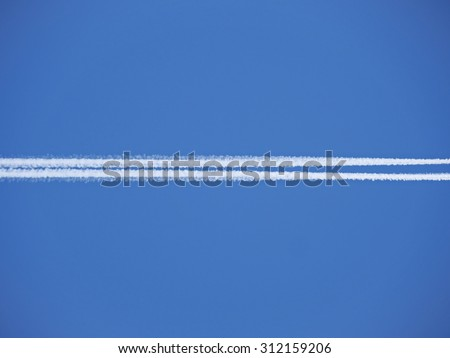 The exhaust trail behind a large aircraft high in the atmosphere - stock photo