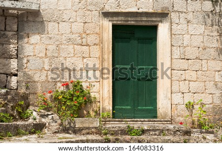 The facade of an old rustic building with a green door