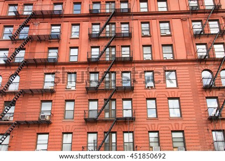 The facade of Manhattan upper east side apartment building with steel fire escape ladders