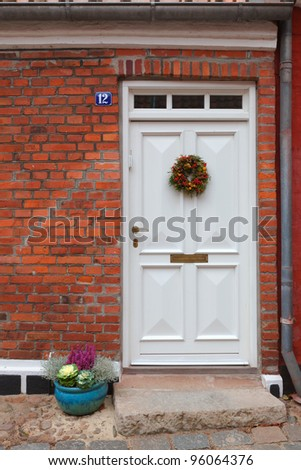 The facade of the house with a white door and brick wall