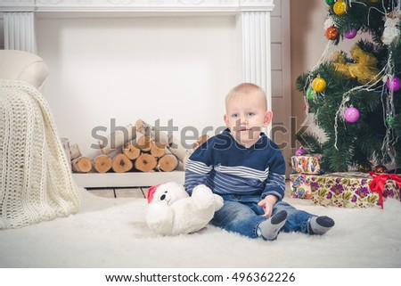 The fair boy sits by the fireplace in Christmas