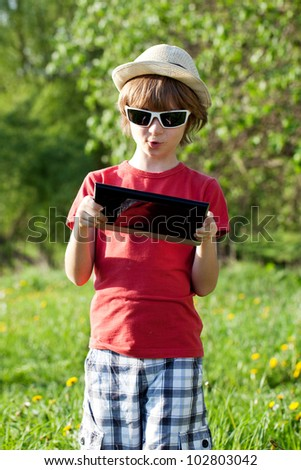 The fair-haired boy in a hat with a computer on the nature - stock photo