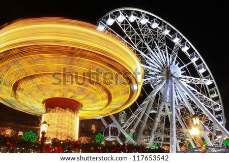 The fair in motion six and big wheel, George Square, Glasgow, Scotland, part of the Christmas and Hogmanay holiday attractions, at night - stock photo